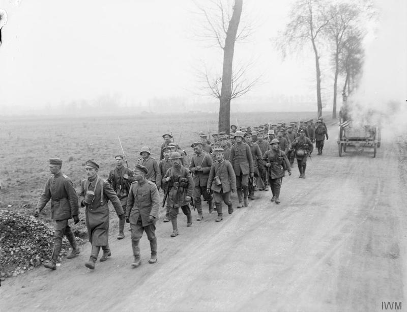 German prisoners captured at the Battle of St. Quentin, marched by a Rifle Brigade escort from the 20th (light) Division, along the Roye-Ham road, 22 March 1918. Imperial war Museum image Q10772.