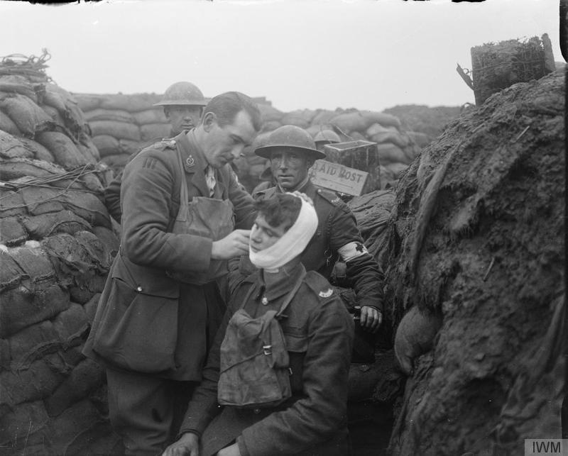The Medical Officer (of the Royal Army Medical Corps attached to the 12th (Service) Battalion, East Yorkshire Regiment (92nd Brigade, 31st Division)) bandaging the face wound of a man of his battalion in the line in the Arleux sector near Roclincourt[Arras], 9 January 1918. Imperial War Museum image Q11545