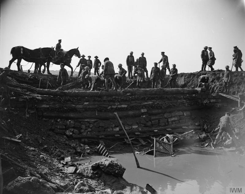 Engineers of the 2nd Battalion, Monmouthshire Regiment (Pioneers of the 29th Division) and trench mortar battery personnel of the 29th Division repairing plank road to left of Hooge, building inside of mine crater to make wheeled traffic possible, 1 October 1918. [During the final offensive in Flanders]. Imperial War Museum image Q11781