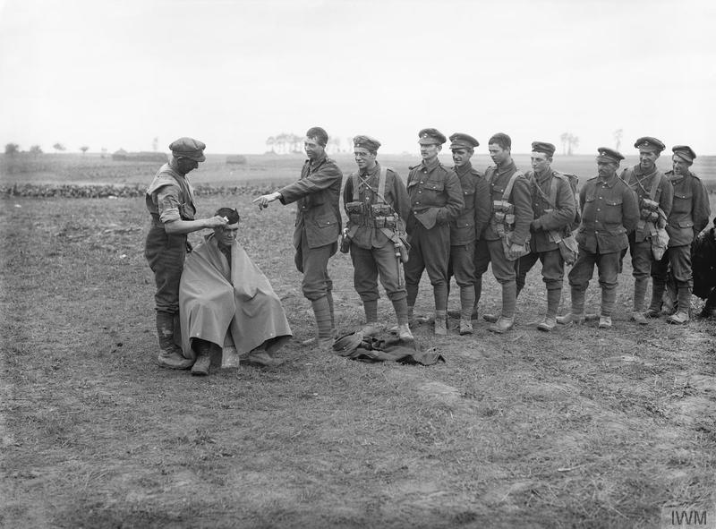 Troops of the 1/5th Battalion, Northumberland Fusiliers waiting for their turn for a hair cut. Toutencourt, October 1916. Imperial War Museum image Q1366