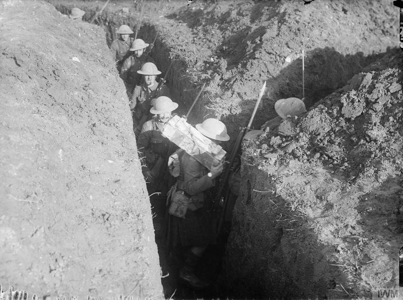 Cameron Highlanders, walk through in a narrow communication trench, situated between Pozieres and Le Sars, in the region of the Battle of the Somme, October 1916. One Highlander carries a box of grenades over his shoulder. Imperial War Museum image Q1497