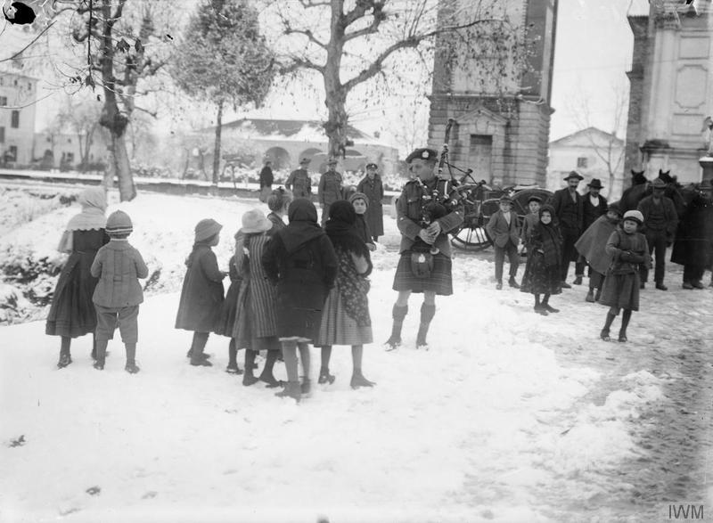 Italian children listening to a piper of the 2nd Battalion, King's Own Scottish Borderers playing in a village. Imperial War Museum image Q26599