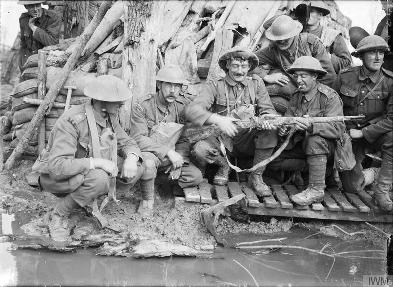 A group of guards, including Coldstream Guards and Irish Guards, crouching outside a captured German dugout, examining a muddy German rifle, near Langemarck (Langemark-Poelkpelle), 12 October 1917. Imperial War Museum image Q3011