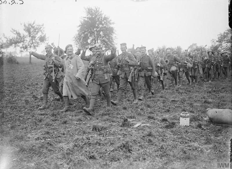 Men of the 1st Battalion, Wiltshire Regiment returning from the attack on Thiepval, 25/26th August 1916, wearing captured German trophies; Bouzincourt. Imperial War Museum image Q3930