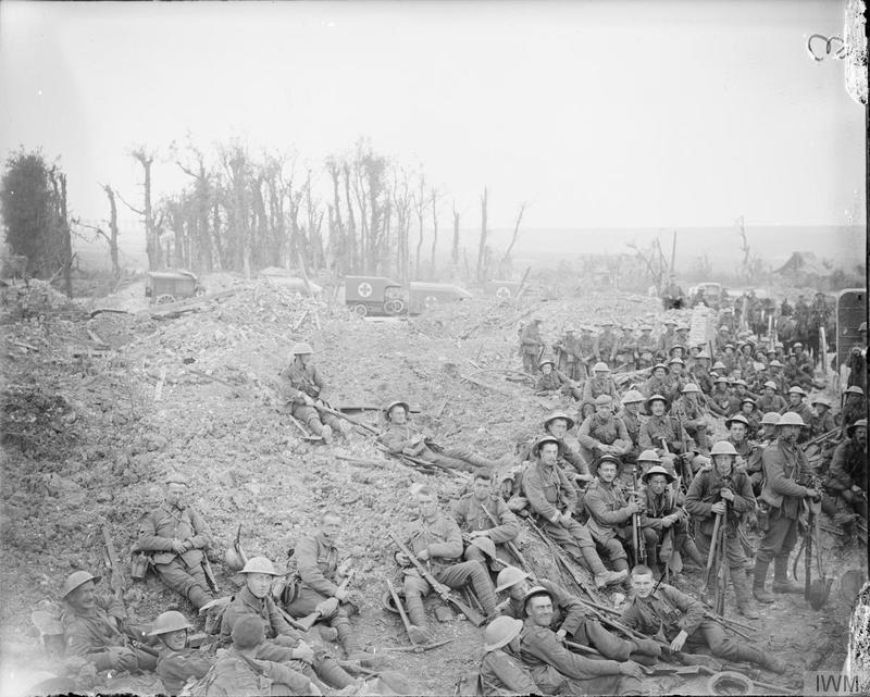 Battle of Bazentin Ridge, Somme. Troops of the 5th Platoon, B Company, 15th Battalion, Hampshire Regiment resting before going into the trenches. Southern Road, Mametz Wood, 17 July 1916. Ambulances of the 63rd Field Ambulance and 2/2nd West Lancashire Field Ambulance (Territorial Force) in the background. Imperial War Museum image Q3978