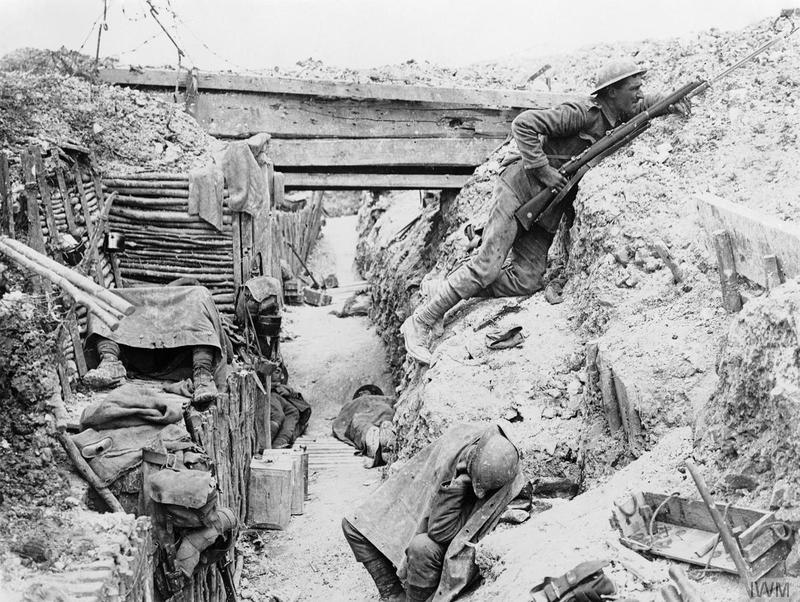 Soldiers of 'A' Company, 11th Battalion, the Cheshire Regiment, occupy a captured German trench at Ovillers-la-Boisselle on the Somme. In this photograph one man keeps sentry duty, looking over the parados and using an improvised fire step cut into the back slope of the trench, while his comrades rest. Imperial War Museum image Q3990