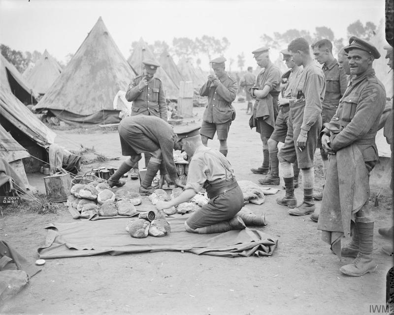 Troops of the 7th (Service) Battalion, Northamptonshire Regiment drawing rations from the Quartermaster's stores in a camp near Dickebusch, 9 August 1917. Imperial War Museum image Q5849