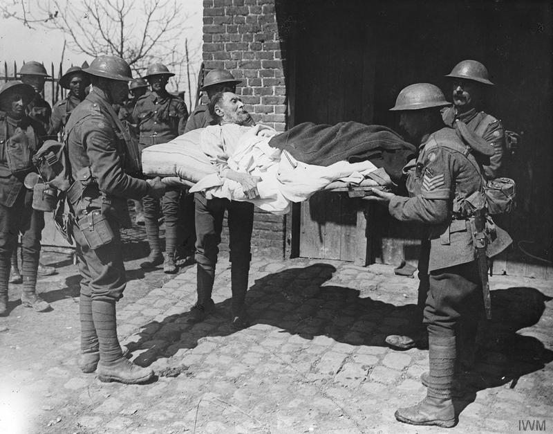 Men of the 2/7th Battalion, Royal Warwickshire Regiment, moving a bed-ridden elderly man of Robecq, 12 April 1918. Imperial War Museum image Q6511. Civilians were being hurriedly evacuated as the German attack - the Battle of the Lys - approached. The units of 61st (2nd South Midland) Division had just arrived to reinforce the area.