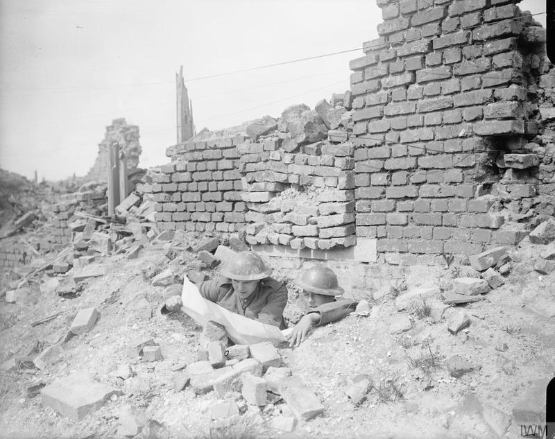 Two men of the King's Royal Rifle Corps (20th Division) checking a map at the entrance to their dug out under a ruined house in Lievin, 14 May 1918. Imperial War Museum image Q6624