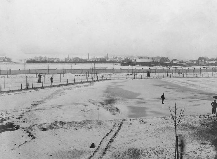 View from Barracks A and B, Holzminden prisoner of war camp. Photograph showing two rows of wire and the outer wall. The sentries were inside the second row of wire. The ground was under snow for several months. Imperial War Museum image Q69485.