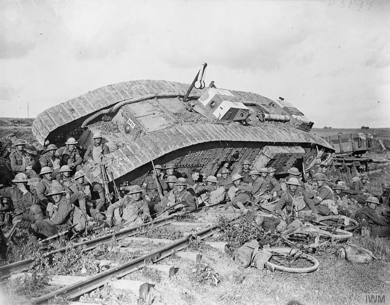 Battle of Cambrai, 1918. Men of the 20th (Service) Battalion, Manchester Regiment resting by a tank (serial number 9891), disabled by side-slipping down a railway embankment. Near Premont, 8 October 1918. Imperial War Museum image Q7113