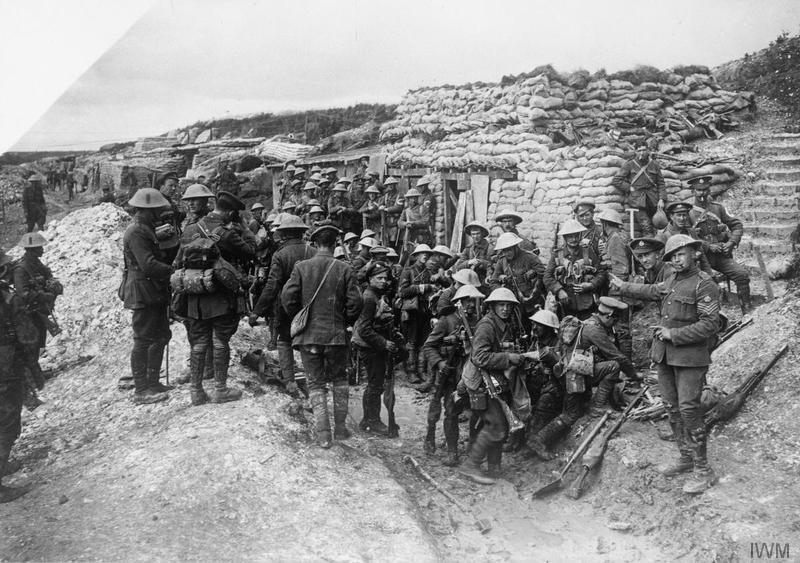 "Staff Sergeant (pointing to his right) of the 16th Battalion, Middlesex Regiment (29th Division) with a group of troops of the 1st Battalion, East Lancashire Regiment, parading at the ""White City"" opposite Hawthorn Ridge for the attack on Beaumont Hamel. Behind them is a party from the 2nd Battalion, Seaforth Highlanders of the 4th Division. Note white cloth carriers ""C"" letter badges on arms of two soldiers from that group. Imperial War Museum image Q796"