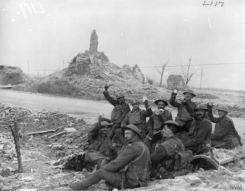Men of a pioneer battalion of the West Yorkshire Regiment, possibly 21st (Service) Battalion (Wool Textile Pioneers), having a meal in a shell hole on the roadside near Ypres, 23 December 1917. Imperial War Museum image Q8441