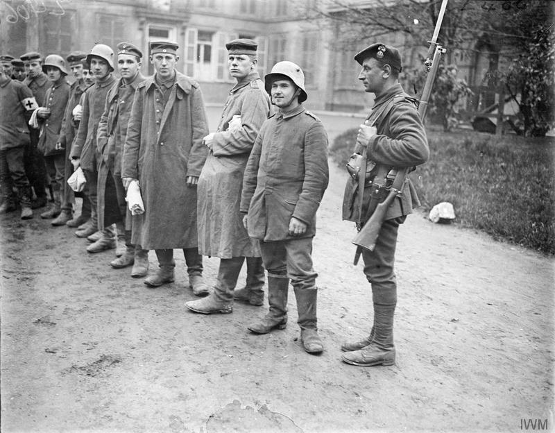 German prisoners, captured near La Bassee, queueing outside a medical inspection hut at Chocques, 10 April 1918. They are being guarded by a Royal Scots Fusilier. Imperial War Museum Q8685