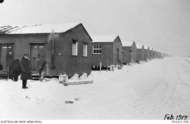 AWM image P02321.059. Lark Hill, Wiltshire, England, February 1917. Snow covers the ground and the roofs of a long row of corrugated iron huts occupied by the 3rd Australian Training Battalion at its camp on Salisbury Plain. The hut in the foreground (left) is the Quartermaster's Office and Store. Standing in front of it is an officer who is well rugged up against the cold.