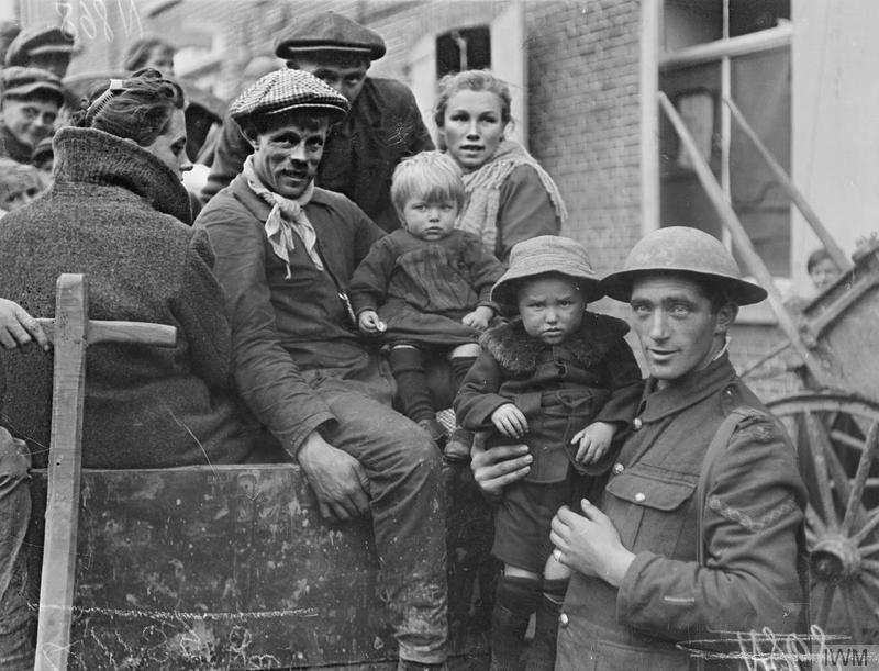 Belgian refugee family in a British horse-drawn wagon. Courtrai, 18 October 1918. British soldier holding one of their children. Imperial War Museum image Q11395. The soldier has a wound stripe.