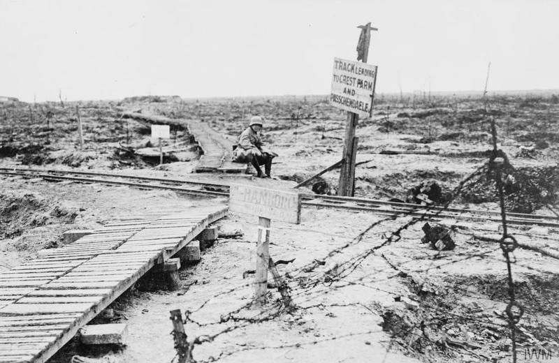 "A German soldier seated on wooden track between Ypres and Passchendaele. Two notice boads read: "" Track leading to Crest Farm and Passchendaele"" and (possibly) ""Hamburg Battalion HQ"". Imperial War Museum made Q57535"