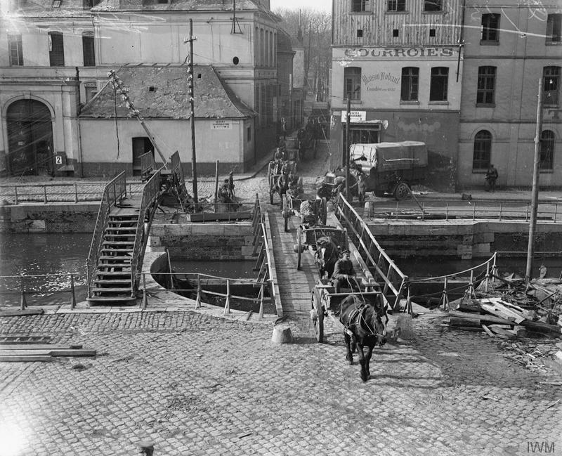 British horse-drawn transport column crossing a temporary bridge over a canal in Douai, 27 October 1918. Douai was occupied on 17 October. Imperial War Museum image Q7155