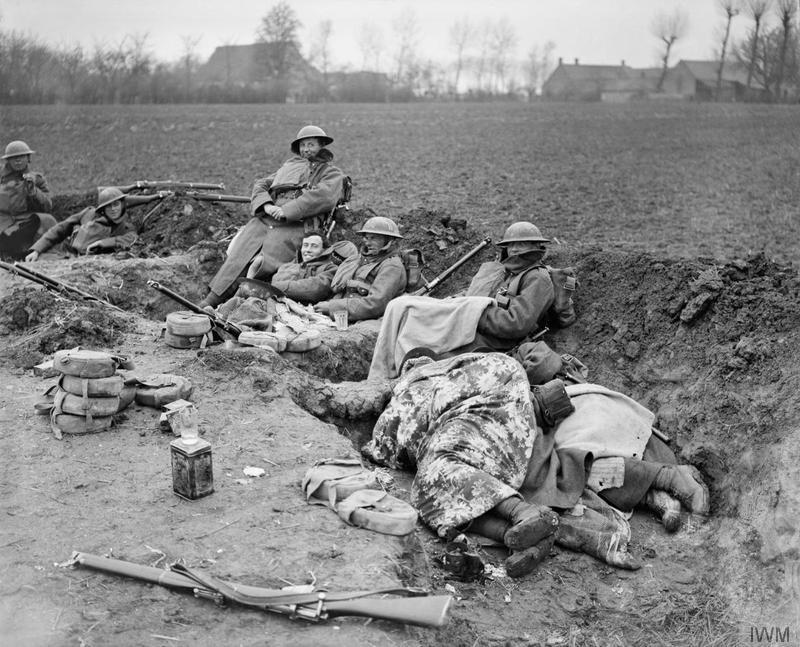 Men of the British 51st (Highland) Division in a hastily dug trench in a ploughed field near Locon. One soldier sleeps beneath a patterned blanket, the others grin at the camera with their equipment scattered around them. Imperial War Museum image Q7854. The Division was rushed into the area on 9 April 1918, to hold the line of the River Lawe.