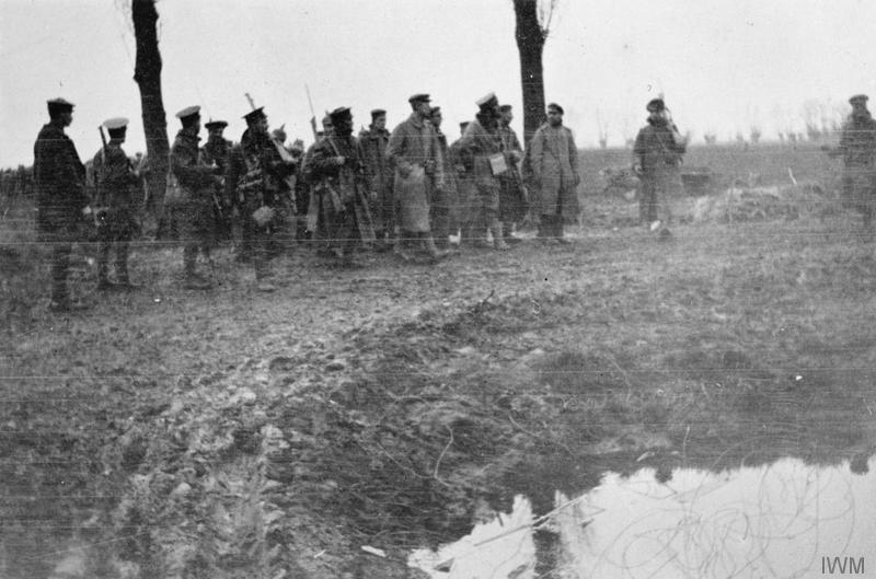 Captured German prisoners guarded by British soldiers at Neuve Chapelle, March 1915. Imperial War Museum image Q90276