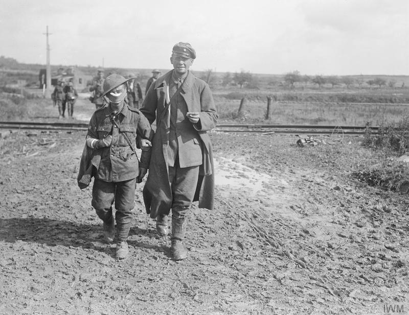 Wounded and Prisoners coming in, near Epehy, 18th September 1918. The wounded soldier in the foreground is from a Bantam unit. Imperial War Museum image Q11329