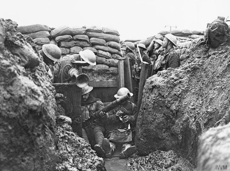 Imperial War Museum image Q4649. Men of the Lancashire Fusiliers sit in a muddy puddle on the floor of a front line trench opposite Messines to clean a Lewis gun. Behind them, as the trench bends round to the right, a group of men can be seen standing in the trench, one of them with his bayonet fixed. To the left of the photographs, can be seen the gas alarm horn and wind vane. Several rows of sandbags form the top left-hand edge of the trench.
