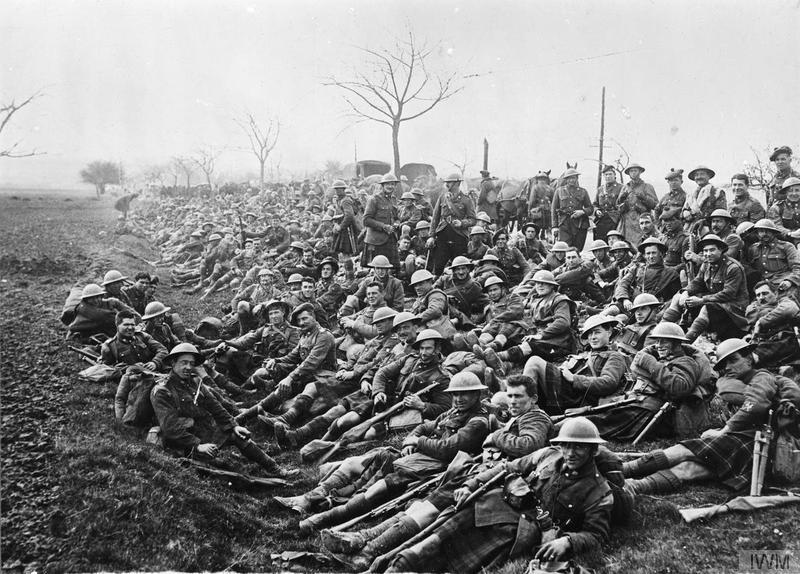 Men of the South African Scottish resting by the side of the road during the march of the South African Brigade out of action at Dernancourt to rest at Condas, 31 March 1918. IWM image Q10843
